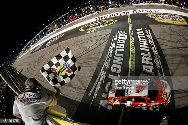 Kevin Harvick driver of the Budweiser Chevrolet takes the checkered flag to win the NASCAR Sprint Cup Series Bojangles' Southern 500 at Darlington...