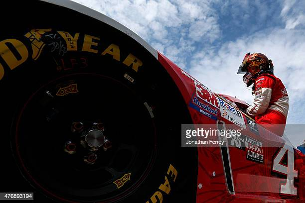 Kevin Harvick driver of the Budweiser/Jimmy John's Chevrolet climbs into his car during qualifying for the NASCAR Sprint Cup Series Quicken Loans 400...