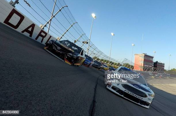 Kevin Harvick driver of the Busch Beer Throwback Ford and Martin Truex Jr driver of the BassProShops/TrackerBoats40thAnv Toyota lead the field under...