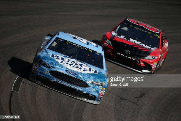 Kevin Harvick driver of the Busch Light Ford leads Corey LaJoie driver of the EJ Wade Construction Toyota during the Monster Energy NASCAR Cup Series...
