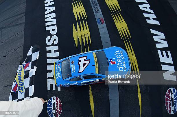 Kevin Harvick driver of the ditech Chevrolet takes the checkered flag to win the NASCAR Sprint Cup Series Bad Boy Off Road 300 at New Hampshire Motor...