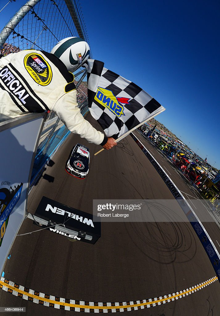 Kevin Harvick, driver of the #4 Jimmy John's/ Budweiser Chevrolet, crosses the finish line to win the NASCAR Sprint Cup Series CampingWorld.com 500 at Phoenix International Raceway on March 15, 2015 in Avondale, Arizona.
