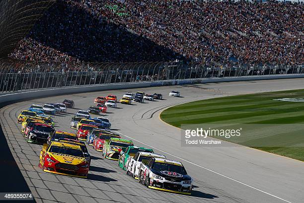 Kevin Harvick driver of the Jimmy John's / Budweiser Chevrolet leads the field at the start of the NASCAR Sprint Cup Series myAFibRiskcom 400 at...