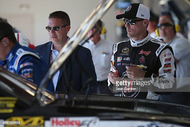 Kevin Harvick driver of the Jimmy John's / Budweiser Chevrolet watches his crew work on his car after blowing a tire and hitting the wall during the...