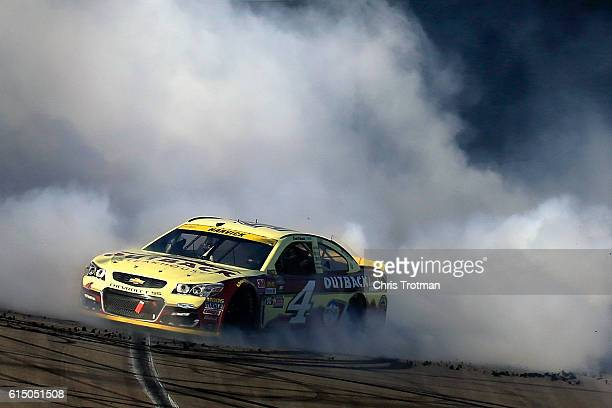 Kevin Harvick driver of the Outback Chevrolet celebrates with a burnout after winning the NASCAR Sprint Cup Series Hollywood Casino 400 at Kansas...