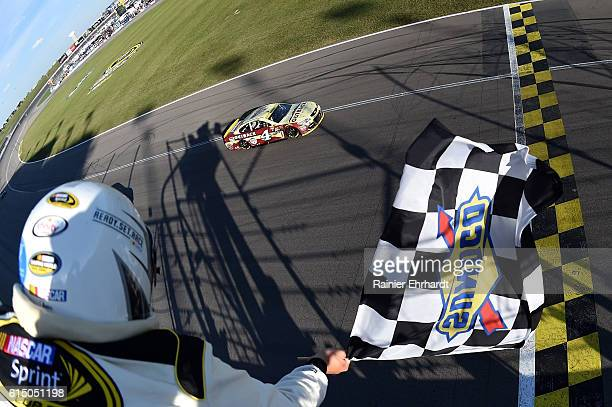 Kevin Harvick driver of the Outback Chevrolet crosses the finish line to win the NASCAR Sprint Cup Series Hollywood Casino 400 at Kansas Speedway on...
