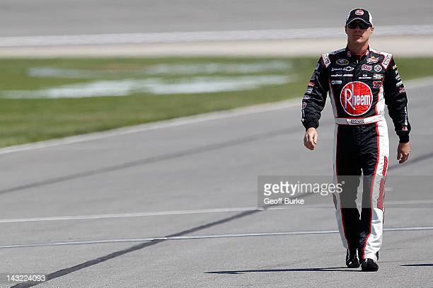 Kevin Harvick driver of the Rheem Chevrolet walks down pit road during qualifying for the NASCAR Sprint Cup Series STP 400 at Kansas Speedway on...