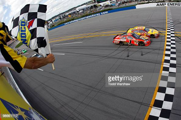 Kevin Harvick driver of the Shell/Pennzoil Chevrolet crosses the finish line ahead of Jamie McMurray driver of the Bass Pro Shops Chevrolet to win...