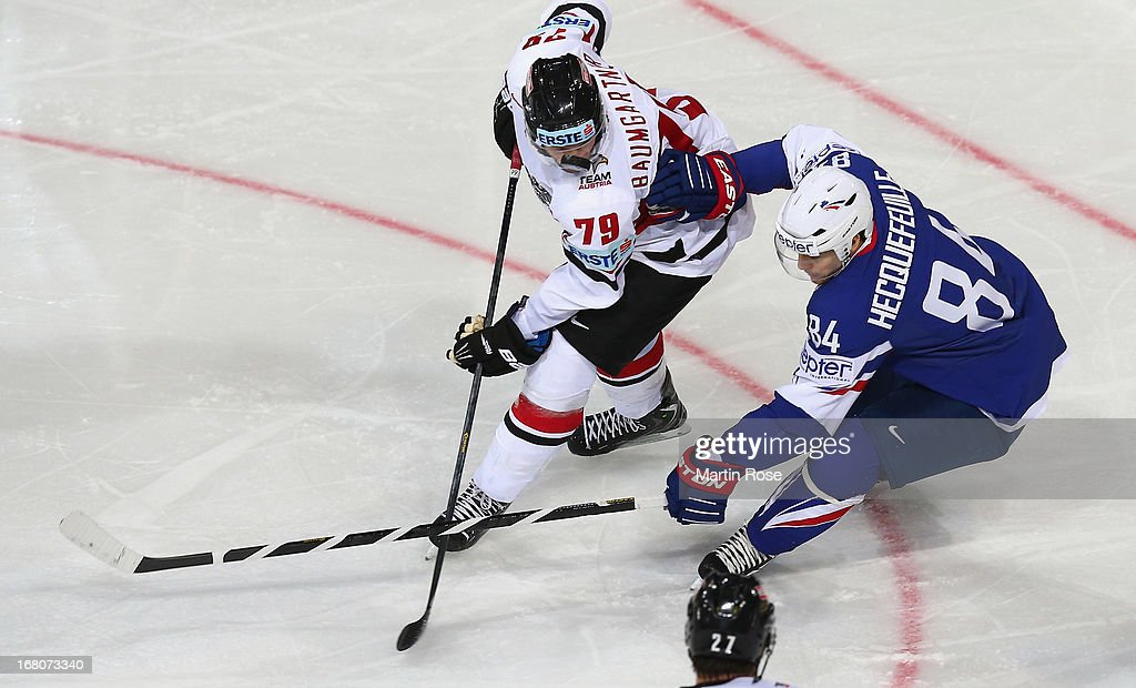 Kevin Hecquefeuille (R) of France and Gregor Baumgartner (L) of Austria battle for the puck during the IIHF World Championship group H match between France and Austria at Hartwall Areena on May 5, 2013 in Helsinki, Finland.