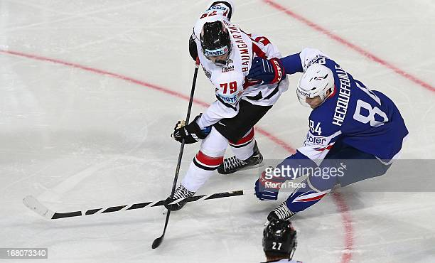 Kevin Hecquefeuille of France and Gregor Baumgartner of Austria battle for the puck during the IIHF World Championship group H match between France...