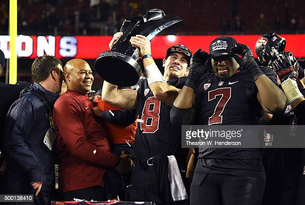 Kevin Hogan of the Stanford Cardinal holding up the championship trophy celebrates with his head coach David Shaw and teammates after they defeated...