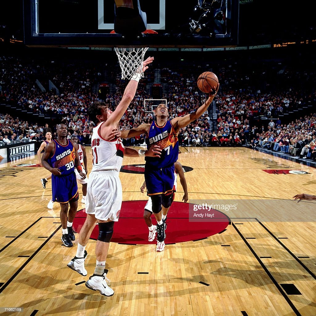 Kevin Johnson of the Phoenix Suns shoots a layup against Arvydas Sabonis of the Portland Trail Blazers at the Rose Garden on November 14 1997 in...