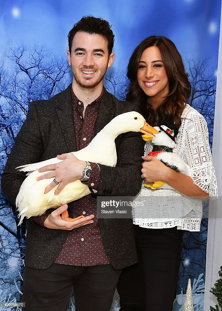 Kevin Jonas and Danielle Jonas and the AFLAC Duck attend #AFLACHOLIDAYHELPERS campaign launch on December 19, 2016 in New York City.