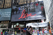 Kevin Jonas and Danielle Jonas look at their images on a jumbotron 'Kiss Cam' during National Lover's Day at the Revlon 'Love is On' popup shop in...