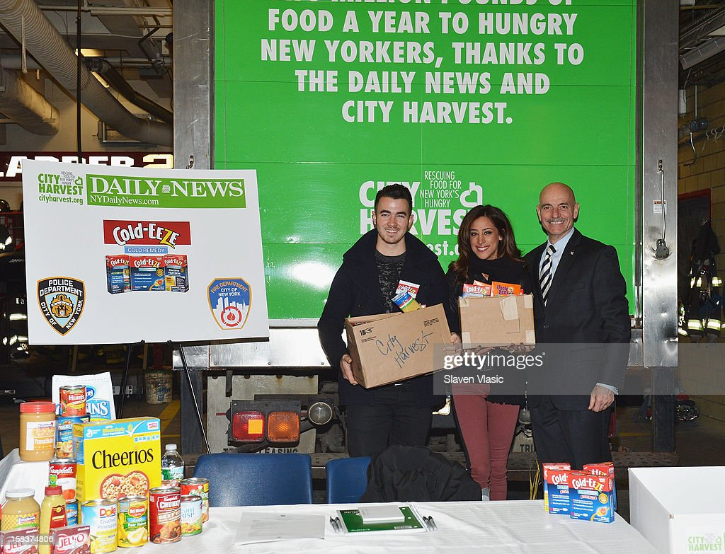 Kevin Jonas, Danielle Jonas and NYC Fire Commissioner Salvatore J. Cassano attend the Kevin Jonas, Danielle Jonas and City Harvest Holiday Season Food Drive at FDNY Station - Lexington & 3rd on December 14, 2012 in New York City.
