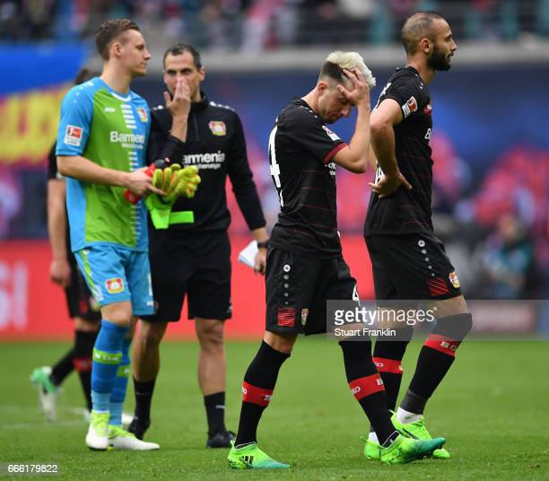 Kevin Kampl and mer Toprak of Leverkusen look dejected during the Bundesliga match between RB Leipzig and Bayer 04 Leverkusen at Red Bull Arena on...