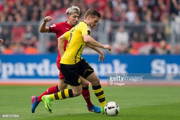 Kevin Kampl of Bayer Leverkusen and Lukasz Piszczek of Dortmund battle for the ball during the Bundesliga match between Borussia Dortmund and Bayer...
