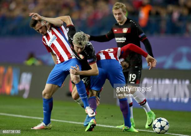 Kevin Kampl of Bayer Leverkusen is challenegd by Saul Niguez of Atletico Madrid during the UEFA Champions League Round of 16 second leg match between...