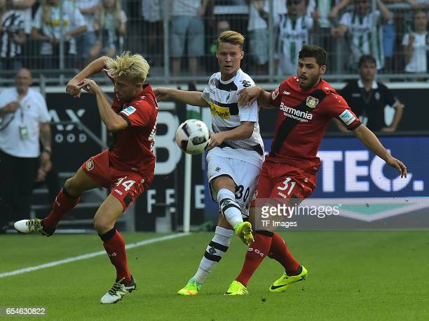 Kevin Kampl of Leverkusen and Nico Elvedi of Moenchengladbach and Kevin Volland of Leverkusen battle for the ball during the Bundesliga match between...