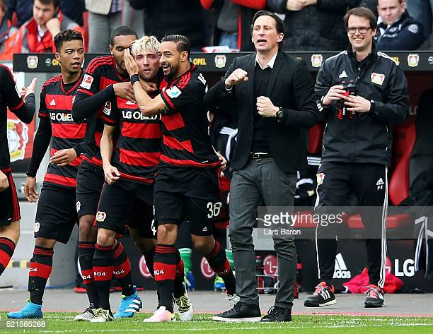 Kevin Kampl of Leverkusen celebrates next to head coach Roger Schmidt after scoring his teams first goal during the Bundesliga match between Bayer...