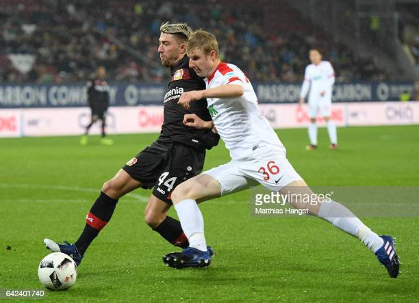 Kevin Kampl of Leverkusen is challenged by Martin Hinteregger of Augsburg during the Bundesliga match between FC Augsburg and Bayer 04 Leverkusen at...