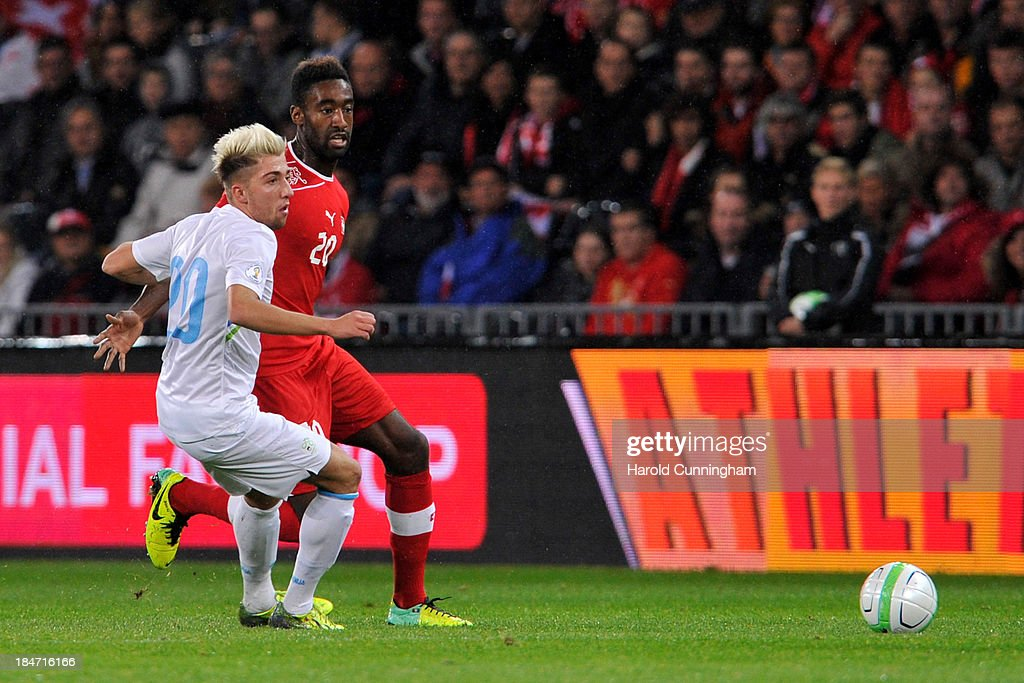 Kevin Kampl of Slovenia and Johannes Djourou of Switzerland in action during the FIFA 2014 World Cup Qualifier match between Switzerland and Slovenia match held at Stade de Suisse on October 15, 2013 in Bern, Switzerland.