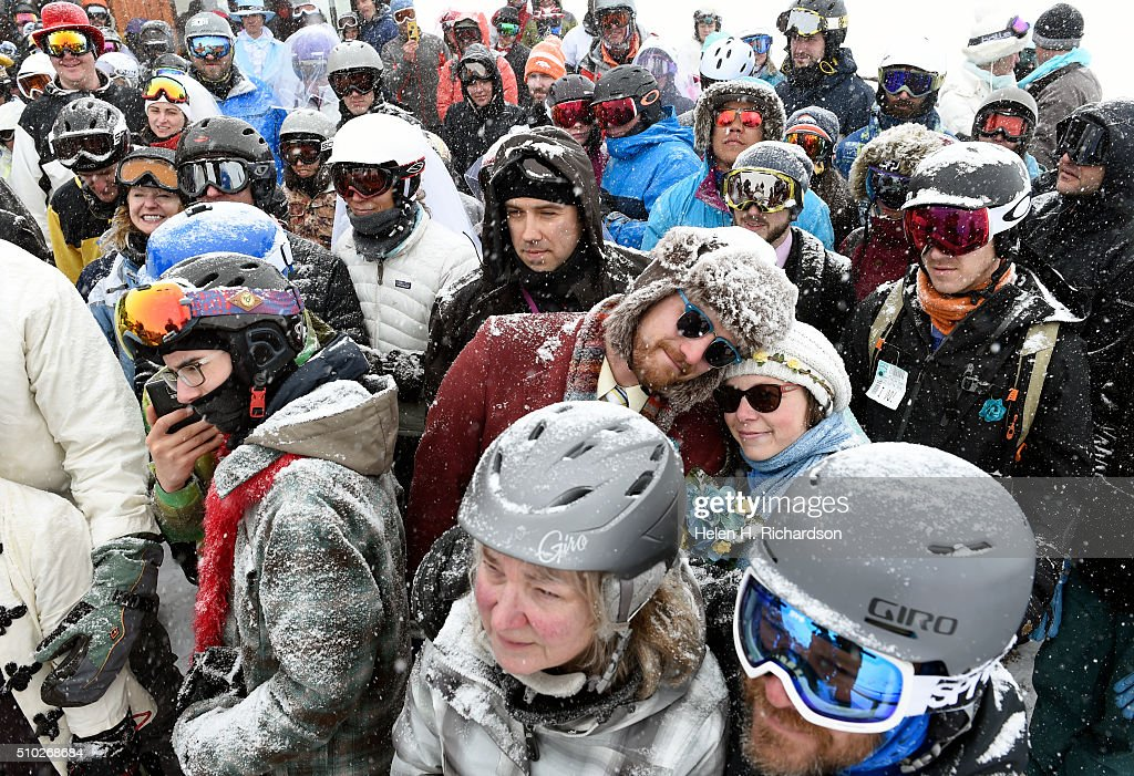 Kevin Kern, in brown suit and his new wife Megan Gilliland, in blue with sunglasses and bouquet of flowers, put their heads together as vows are read during the 25th annual Mountaintop Matrimony Valentine's day wedding ceremony on February 14, 2016 at the Loveland Ski area near Georgetown, Colorado. The couple came from Denver to get married at the ski area. The ceremony was held at Ptarmigan Roost cabin at the top of Ptarmigan lift. Approximately 100 couples got married or renewed their vows with minister Harry Heilmann, of the Universal Life Church, overseeing the ceremony.