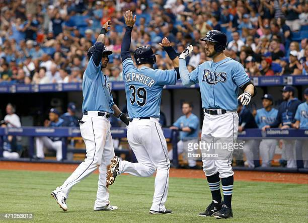 Kevin Kiermaier of the Tampa Bay Rays celebrates with teammates Tim Beckham and Steven Souza Jr #20 after scoring off of a single by Brandon Guyer...