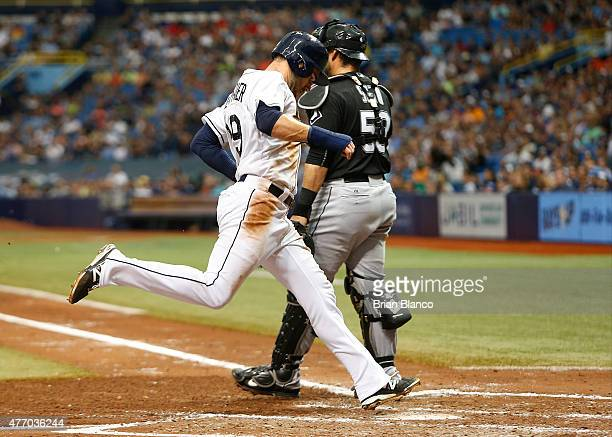 Kevin Kiermaier of the Tampa Bay Rays crosses home plate in front of catcher Geovany Soto of the Chicago White Sox to score following the ground out...