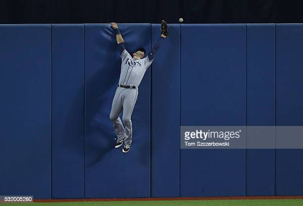 Kevin Kiermaier of the Tampa Bay Rays leaps but cannot get to a tworun home run in the first inning during MLB game action off the bat of Jose...
