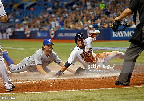 Kevin Kiermaier of the Tampa Bay Rays slides across home plate ahead of pitcher RA Dickey of the Toronto Blue Jays to score off Dickey's wild pitch...