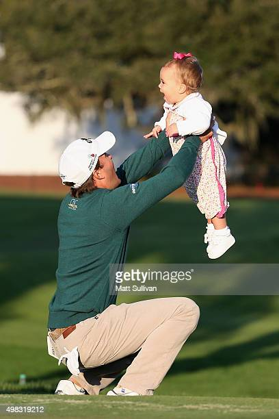 Kevin Kisner celebrates with his daughter Kathleen on the 18th green of the Seaside Course after winning The RSM Classic on November 22 2015 in St...