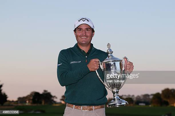 Kevin Kisner celebrates with the winner's trophy on the 18th green of the Seaside Course after winning The RSM Classic on November 22 2015 in St...