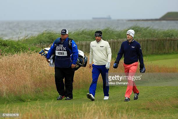 Kevin Kisner of the United States and his caddie Devin Bock walk with Russell Knox of Scotland during the third round on day three of the 145th Open...