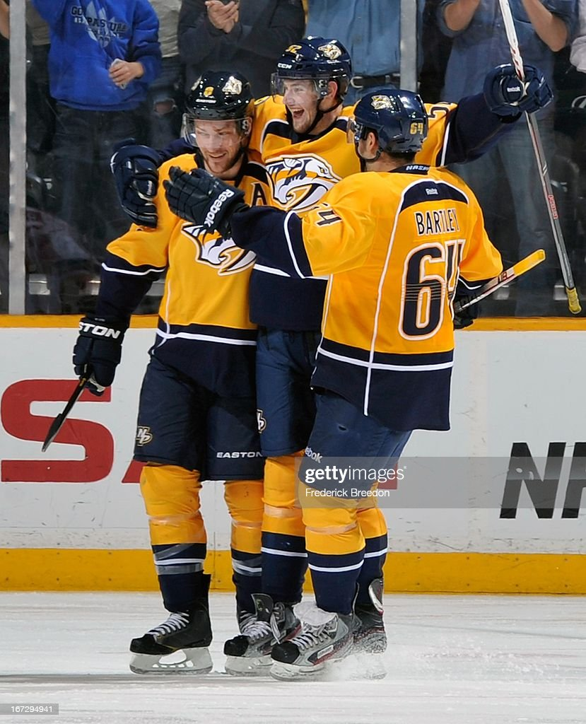 Kevin Klein #8 and Victor Bartley #64 of the Nashville Predators congratulate teammate Austin Watson #52 on scoring his first career NHL goal against the Calgary Flames at the Bridgestone Arena on April 23, 2013 in Nashville, Tennessee.