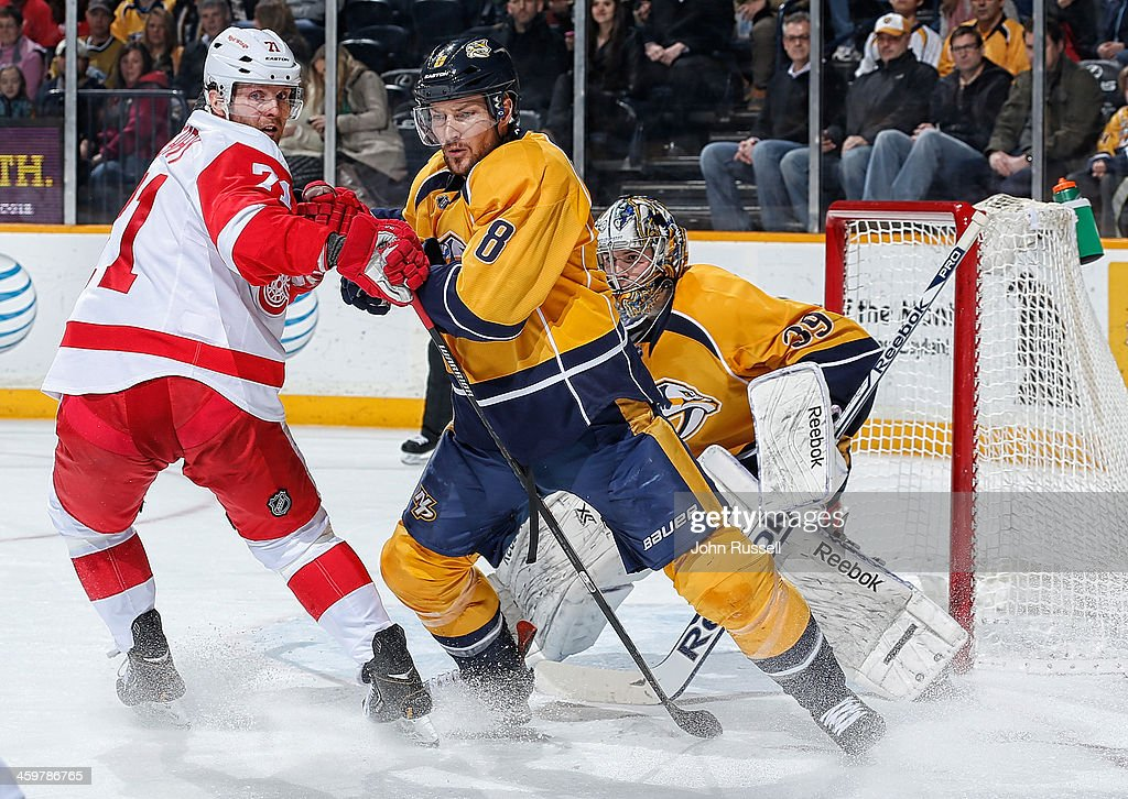 Kevin Klein #8 of the Nashville Predators battles against <a gi-track='captionPersonalityLinkClicked' href=/galleries/search?phrase=Daniel+Cleary&family=editorial&specificpeople=220490 ng-click='$event.stopPropagation()'>Daniel Cleary</a> #71 of the Detroit Red Wings in front of Predators goalie Marek Mazanec #39 at Bridgestone Arena on December 30, 2013 in Nashville, Tennessee.