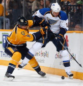 Kevin Klein of the Nashville Predators battles along the boards against Keith Aucoin of the St Louis Blues at Bridgestone Arena on October 26 2013 in...