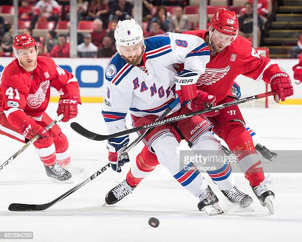 Kevin Klein of the New York Rangers skates after a loose puck in front of Thomas Vanek of the Detroit Red Wings during an NHL game at Joe Louis Arena...