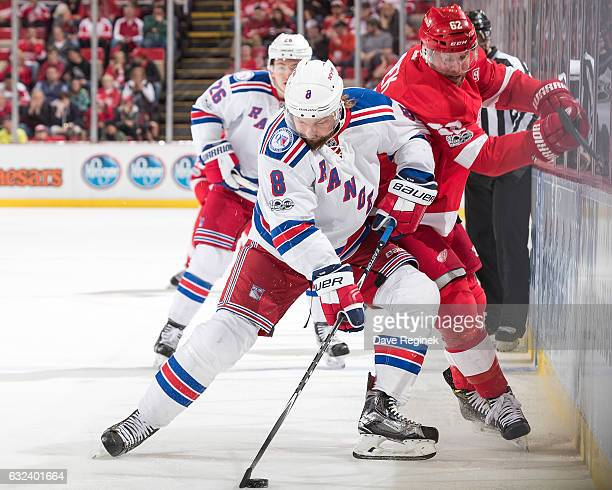 Kevin Klein of the New York Rangers skates with the puck along the boards followed by Thomas Vanek of the Detroit Red Wings during an NHL game at Joe...