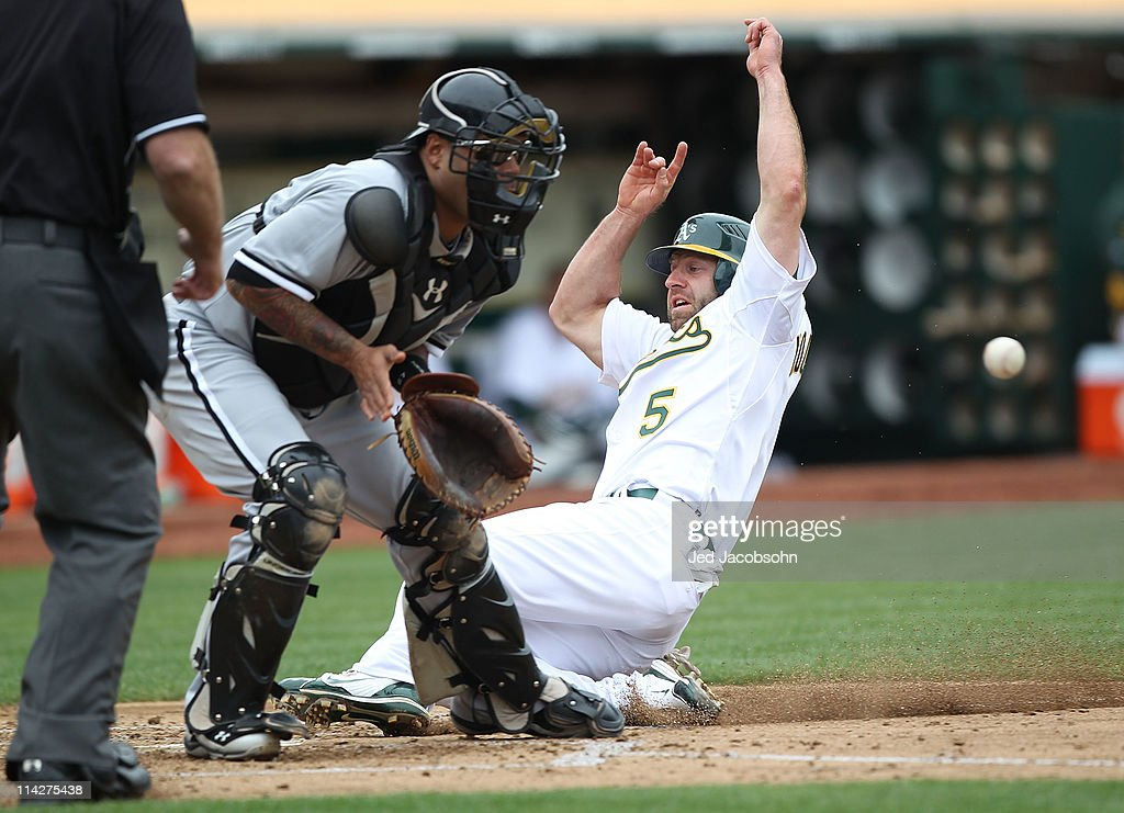 Kevin Kouzmanoff #5 of the Oakland Athletics slides home past Ramon Castro #27 of the Chicago White Sox during a Major League Baseball game at the Oakland-Alameda County Coliseum on May 14, 2011 in Oakland, California.