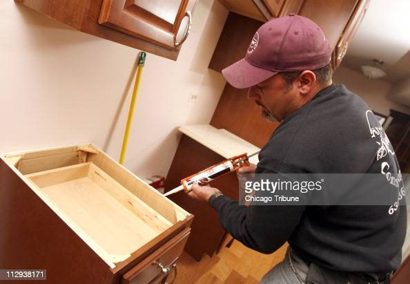 Kevin Krueger lays down a bead of caulk before installing a countertop during a kitchen remodel in Naperville Illinois on October 10 2007