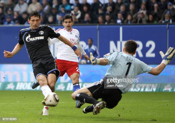 Kevin Kuranyi of Schalke shoots against goalkeeper Frank Rost and Tomas Rincon of Hamburg during the Bundesliga match between Hamburger SV and FC...