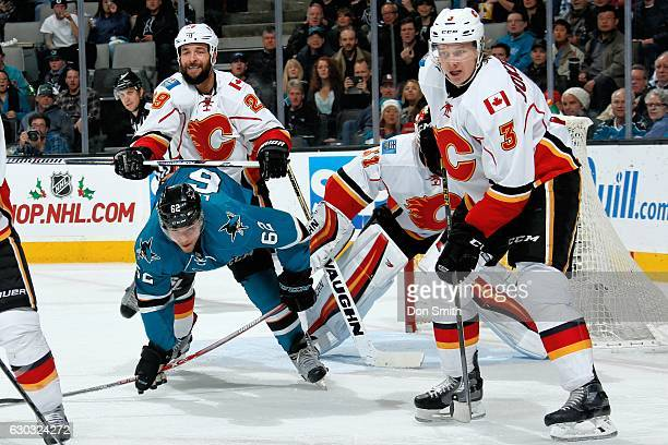 Kevin Labanc of the San Jose Sharks is checked by Deryk Engelland of the Calgary Flames as Jyrki Jokipakka and Chad Johnson of the Calgary Flames...