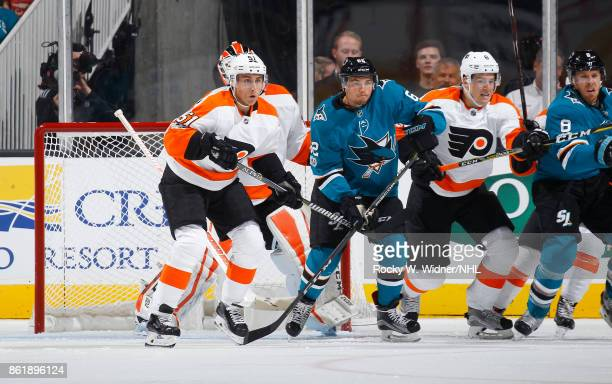 Kevin Labanc of the San Jose Sharks is defended by Valtteri Filppula and Robert Hagg of the Philadelphia Flyers at SAP Center at San Jose on October...