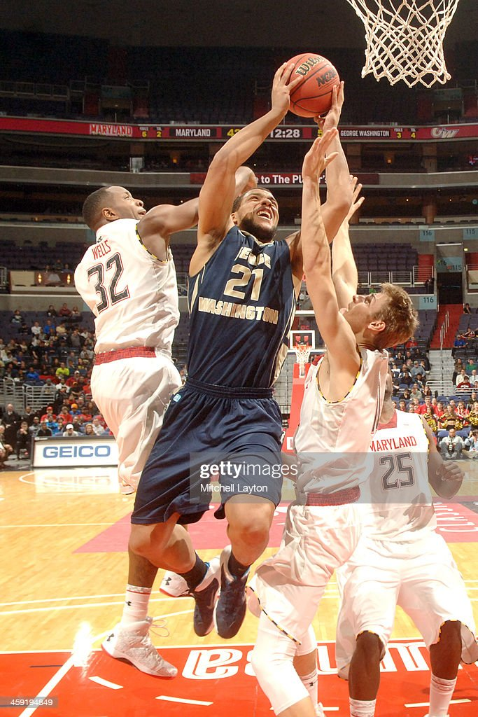 Kevin Larsen of the George Washington Colonials drives to the basket through Dez Wells and Jake Layman of the Maryland Terrapins during the BBT...