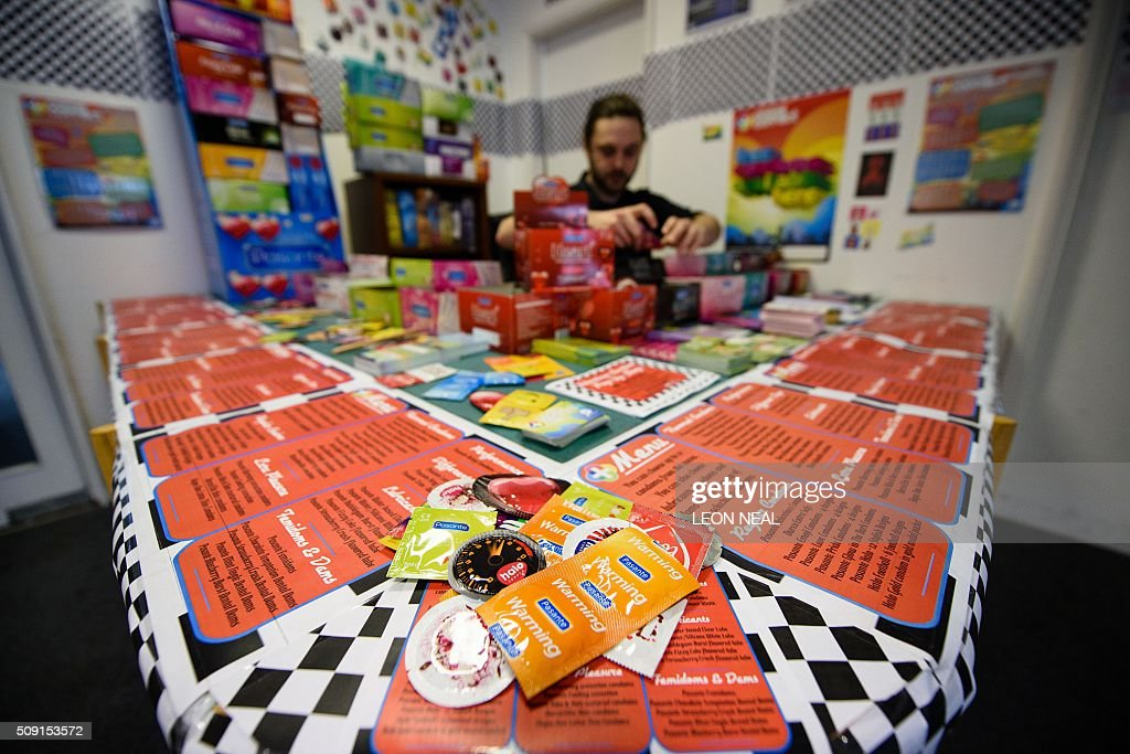 Kevin Lennon of 'Come Correct' poses with a display of the condoms available at the Valentine's Condom pop-up shop in east London on February 9, 2016. 'Come Correct' are hosting a free pop-up shop leading up to Valentine's day from February 8-13. Come Correct is the London-based condom distribution service where young people can access free condoms using a special 'c-card' in many locations across the capital. The scheme is run by the young people's charity Brook and has over 80 locations across the borough of Hackney where young people can pick up free contraceptives. The condoms are available in a huge range of colours and flavours including 'Blueberry Blast', apple, 'Mint Tingle' and 'Bubblegum Blast'. / AFP / LEON NEAL