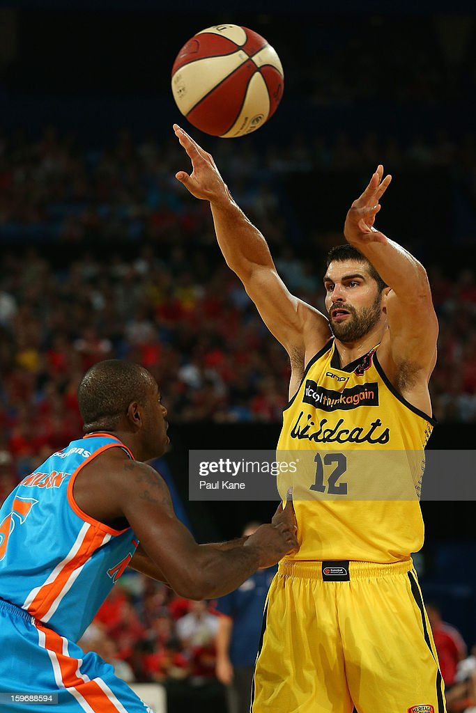 Kevin Lisch of the Wildcats passes the ball against Jamar Wilson of the Taipans during the round 15 NBL match between the Perth Wildcats and the Cairns Taipans at Perth Arena on January 18, 2013 in Perth, Australia.