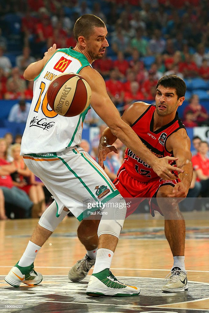 Kevin Lisch of the Wildcats passes the ball around Russell Hinder of the Crocodiles during the round 16 NBL match between the Perth Wildcats and the Townsville Crocodiles at Perth Arena on January 25, 2013 in Perth, Australia.