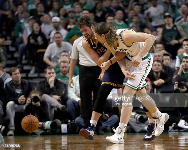Kevin Love of the Cleveland Cavaliers injures his shoulder as he chases a loose ball against Kelly Olynyk of the Boston Celtics in the first half in...