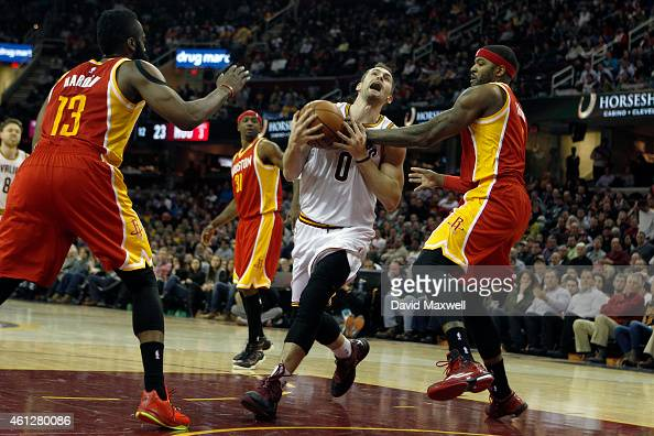 Kevin Love of the Cleveland Cavaliers is defended by James Harden and Josh Smith of the Houston Rockets during the first half of their game on...